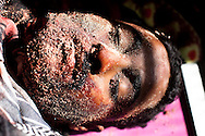 A volunteer soldier covers the face of a man killed in battle with Qadaffi troops in Brega on March 2, 2011. man killed in battle with Qadaffi troops in Brega on March 2, 2011.