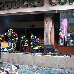 Fire fighters leave a destroyed Starbucks after putting out a fire started by rioters.