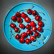 Bunch of cherries with stems on a blue plate, in studio, dark food photography
