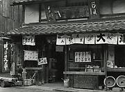 "Asano Kiichi<br /> 1914 - 1993<br /> <br /> Shop front, Otsu, Shiga Prefecture, 1950s.<br /> <br /> On the reverse is Asano's official red hanko stamp and an inscription in the artist's hand: ""Otsu e no mise"" (translation: picture of shop in Otsu (Shiga Prefecture).<br /> <br /> Vintage gelatin silver print.<br /> <br /> Size 4 3/4 in. x 6 1/2 in. (120 mm x 165 mm).<br /> <br /> Condition very good.<br /> <br /> Price ¥90,000<br /> <br /> <br /> <br /> <br /> <br /> <br /> <br /> <br /> <br /> <br /> <br /> <br /> <br /> <br /> <br /> <br /> <br /> <br /> <br /> <br /> <br /> <br /> <br /> <br /> <br /> <br /> ."