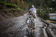 A woman from the Ethiopian Highlands carries a heavy sack of wheat, aid from the United States to ward off famine, despite the return of the rains.  After suffering one of the worst droughts in decades, now the Northern Ethiopian Highlands are experiencing heavy rains, as the pendulum has swung back the other way, creating worry about crop failures due to the rains.  USAID has designated this region of the highlands as having a high to extreme risk of food insecurity, hence the food distribution.  Northern Ethiopian Highlands.