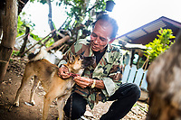 Kawai Thanthongdee plays with his pet dog outside of his home in Sakon Nakhon, Thailand. Mr. Kawai's wife was arrested and fined for operating a small family-run dog meat restaurant. The family does not consider their pet dogs as food.