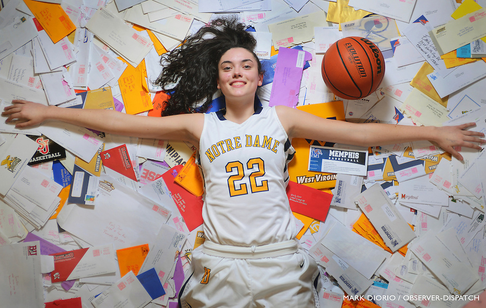 Notre Dame High School varsity girls basketball player Emily Durr sits among many letters of interest that she has received from colleges and universities around the countyr, Jan. 8, 2013, in Utica, N.Y.