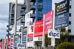 Many sign boards from estate agents for properties for sale and rent outside large modern apartment blocks at western Harbour in Leith, Edinburgh, Scotland, UK