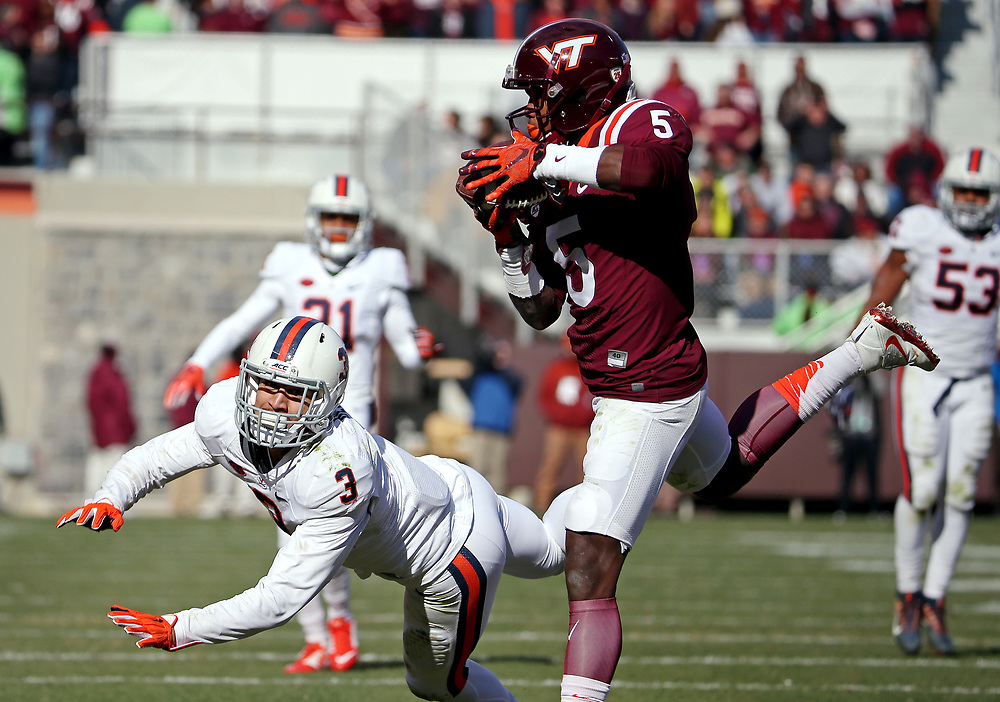 Nov 26, 2016; Blacksburg, VA, USA;  Virginia Tech Hokies wide receiver Cam Phillips (5) catches a touchdown pass against Virginia Cavaliers safety Quin Blanding (3) during the second quarter at Lane Stadium. Mandatory Credit: Peter Casey-USA TODAY Sports