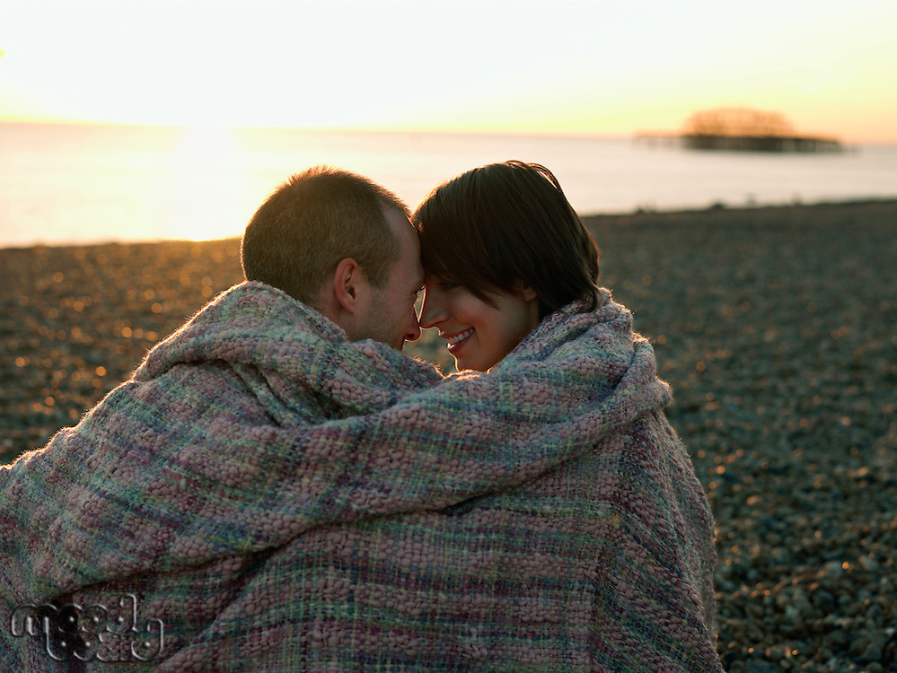 Couple wrapped in blanket sitting on beach at sunset