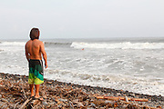 surfer on the beach studies the swell. Photographed at El Tunco beach, El Salvador,
