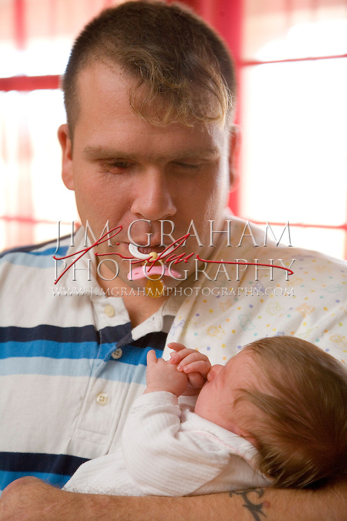 Jason Pepper rocks  his new born daughter, Cheyenne Noelle, after feeding her in the kitchen of their home in Primm Springs, TN., Monday Nov. 20, 2006. Photo by Jim Graham.