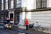 In Dordrecht praten twee postbestellers van PostNL met een oudere vrouw op de fiets.<br /> <br /> In Dordrecht two mailmen talk to an elderly woman on a bike.