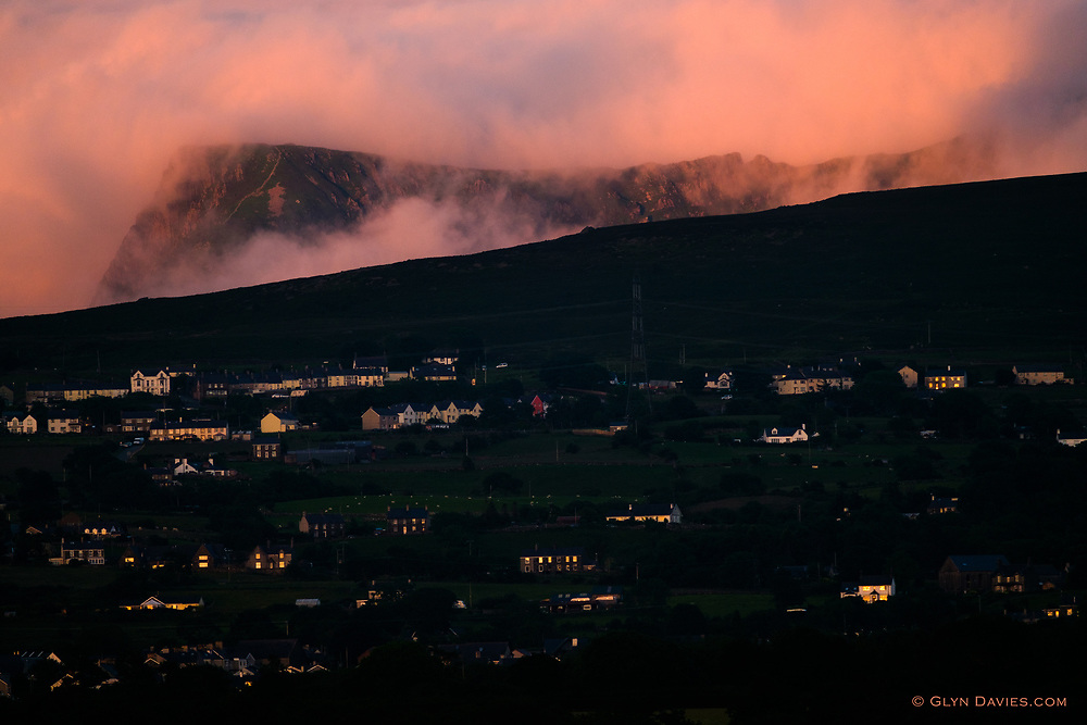 The last embers of a burning sunset caught the gable ends of the hillside town of Groeslon on the hillside below the imposing Nantlle Ridge. The clouds were on fire, billowing and swirling, hiding and revealing the majestic hills behind. <br />