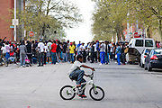 Baltimore, Maryland - April 20, 2015: A child on a bicycle rides by demonstrators gathered outside the Western District Police Station in Baltimore Monday to protest the death of Freddie Gray.<br /> <br /> <br /> CREDIT: Matt Roth for The New York Times<br /> Assignment ID: 30173608A
