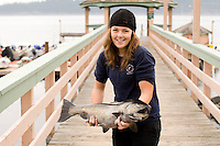 A young employee at Painter's Lodge in Campbell River displays a Chinook Salmon,  caught in the water's around Quadra Island. CAmpbell River, Vancouver Island, British Columbia, Canada.