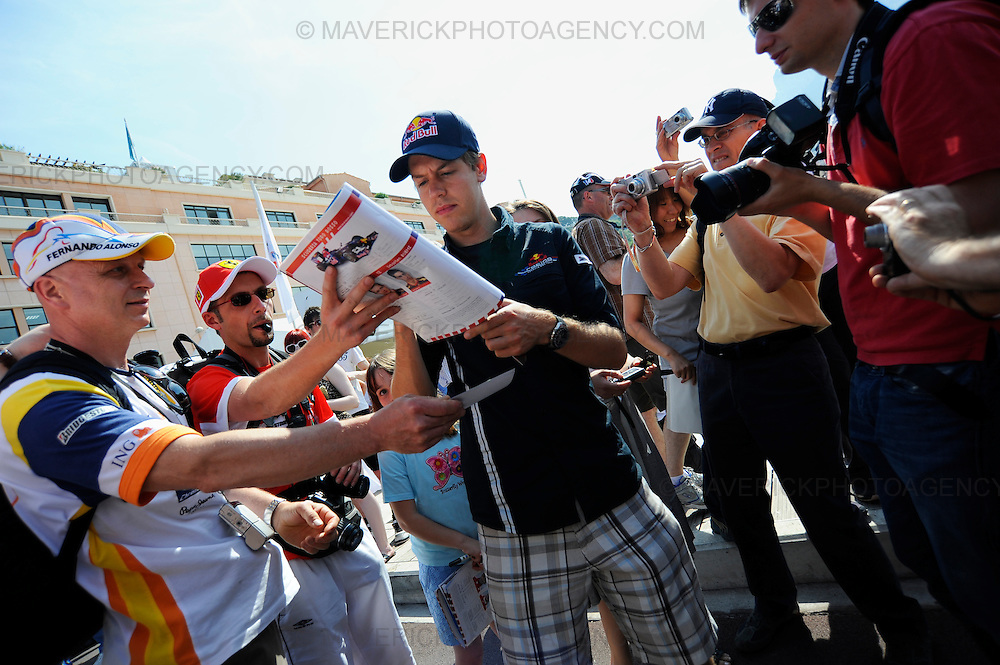 Red Bull Racing driver Sebastian Vettel signs autographs for fans at the Monaco Grand Prix.