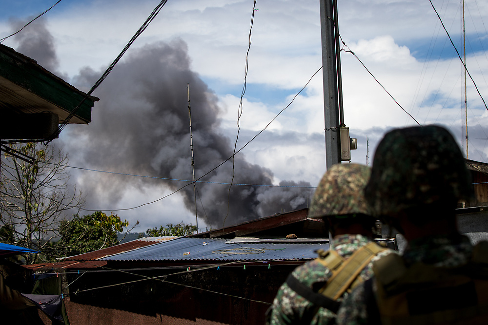 MARAWI, PHILIPPINES - JUNE 9: Philippine marines look at smoke following an airstrikes by Philippine Air Force in Marawi, southern Philippines on June 9, 2017. Philippine military jets fired rockets at militant positions on Friday as soldiers fought to wrest control of the southern city from gunmen linked to the Islamic State group.(Photo: Richard Atrero de Guzman/NUR Photo)