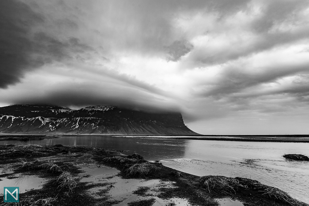 A blanket of cloud covers the top of Lómagnúpur cliff in southern Iceland.