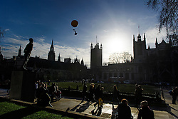 © Licensed to London News Pictures. 06/01/2017. London, UK. An image of Mary Poppins wearing a face mask is suspended from a balloon over Parliament Square in front of the Houses of Parliament in London during a protest about air pollution by Greenpeace. Photo credit: Ben Cawthra/LNP