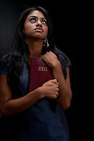 Young woman looking up very faithful and holding the bible.
