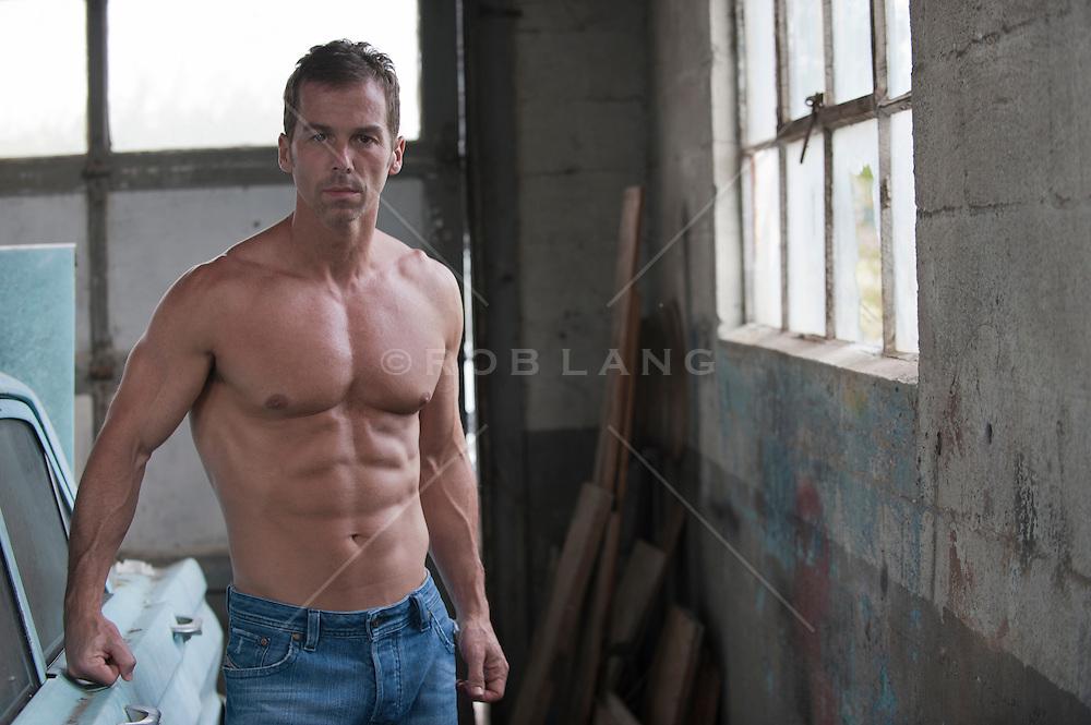 shirtless muscular man in an abandoned garage