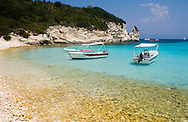A view of boats and limestone cliffs at Mesovrika Beach on the northeast side of Anti-Paxos, Ionian Islands, Greece