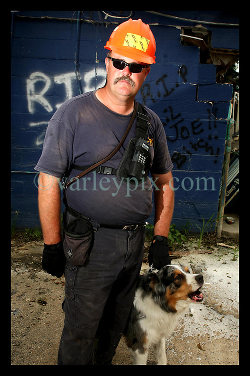 May 5th, 2006. Lower 9th Ward, New Orleans, Louisiana. Over 8 months after hurricane Katrina and still the city remains largely in ruins in many devastated neighbourhoods. Wayne Buford, director of the State Emergency Management Agency with his dog Rusty outside a building tagged with RIP graffiti. Buford is in charge of the grim task of body recovery from the ruins of the the Lower 9th Ward. His dog Rusty is a trained cadaver dog, used to sniff out human remains still buried in the rubble. They continue to find skeletal remains.