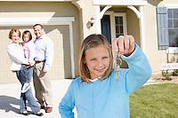 Girl (7-9) holding keys, rest of family in background
