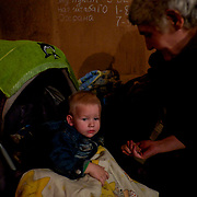 A local IDP comforts a child at a Soviet era bomb shelter in Petrovskiy district, Donetsk. The daily routine of the almost hundred people living here for the past four months, can be tedious as the regular shellfire between DNR rebels and the Ukrainian National Guard is a constant threat that constrain them to stay underground most of the time.