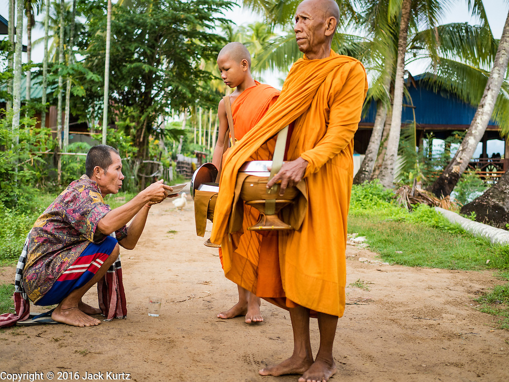 "20 JUNE 2016 - DON KHONE, CHAMPASAK, LAOS:  A man makes an offering to monks from Wat Khone Nua on their morning alms' rounds, called the ""tak bat"" in Don Khone village on Don Khone Island. Don Khone Island, one of the larger islands in the 4,000 Islands chain on the Mekong River in southern Laos. The island has become a backpacker hot spot, there are lots of guest houses and small restaurants on the north end of the island.    PHOTO BY JACK KURTZ"