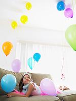 Young girl (7-9) lying on sofa looking at balloons