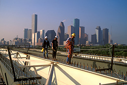 Stock photo of workers near downtown Houston balance on a steel girder and wald between steel bolts.