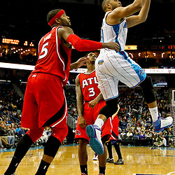 Jan 1, 2013; New Orleans, LA, USA; New Orleans Hornets shooting guard Eric Gordon (10) shoots over Atlanta Hawks small forward Josh Smith (5) and shooting guard Louis Williams (3) during the second half of a game at the New Orleans Arena. The Hawks defeated the Hornets 95-86. Mandatory Credit: Derick E. Hingle-USA TODAY Sports