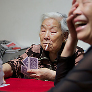 Former farmers play cards in southern China in her newly furnished apartment given by the government in return for seized land.<br /> <br /> China is pushing ahead with a dramatic, history-making plan to move 100 million rural residents into towns and cities over six years &mdash; but without a clear idea of how to pay for the gargantuan undertaking or whether the farmers involved want to move.<br /> <br /> Moving farmers to urban areas is touted as a way of changing China&rsquo;s economic structure, with growth based on domestic demand for products instead of exporting them. In theory, new urbanites mean vast new opportunities for construction firms, public transportation, utilities and appliance makers, and a break from the cycle of farmers consuming only what they produce.<br /> <br /> Urbanization has already proven to be one of the most wrenching changes in China&rsquo;s 35 years of economic reforms. Land disputes rising from urbanization account for tens of thousands of protests each year.