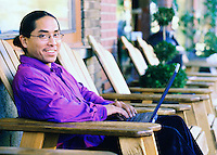 Portrait of a mixed race man sitting outside a cafe working with his laptop computer. Filipino / Hawaiian.
