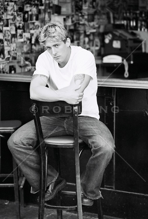 Man sitting on a chair in a bar looking tough