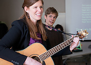 """Meredith Pizzi, left, sings the Bob Marley classic, """"Three Little Birds (Don't Worry)"""" along with a room full of students about to practice pitching business ideas."""