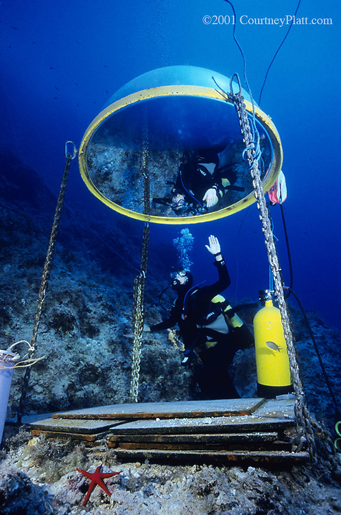 "Archaeologist Deborah Carson demonstrates use of the ""telephone booth"", an emergency air pocket next to the wreck site.  Because the site is 130' deep, it is also useful for underwater conversations when necessary."