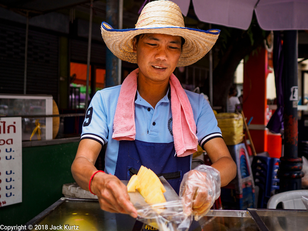 29 JUNE 2018 - BANGKOK, THAILAND: A fruit vender on Soi Wanit 2 near the Chao Phraya River in Bangkok's Chinatown prepares an order of sliced pineapple for a customer.     PHOTO BY JACK KURTZ