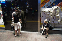 A couple kissing in front of an old lady and of a sculpture of Hachiko the dog, Shibuya station, Tokyo, Japan.