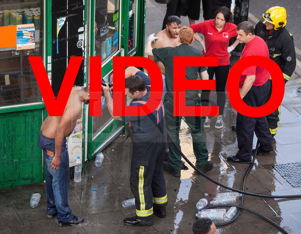 VIDEO AVAILABLE HERE: https://we.tl/ctF0ntAmmz<br /> <br /> © Licensed to London News Pictures. 25/07/2017. London, UK. Two victims of what is thought to have been an acid attack have water poured on their heads by a firemen - on the side of the road in Bethnal Green. Two men have been taken to hospital after flagging down police for help. Photo credit: Liam Creighton/LNP