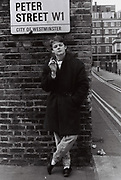Teenage boy standing in front of street sign in Soho, London, UK, 1983