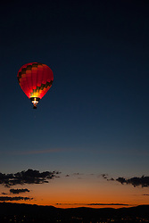 """""""Dawn Patrol 14"""" - Photograph of a glowing hot air balloon flying for the Dawn Patrol at the 2012 Great Reno Balloon Race. Photographed from a hot air balloon."""