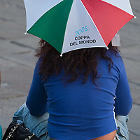 MILAN, ITALY - JUNE 14:  An Italian fan wearing Italy national team jersey and an head umbrella in the Italian flag colours sits in Piazza del Duomo on June 14, 2010 in Milan, Italy. Italy's national football team managed a draw 1-1 against Paraguay in their first match of FIFA 2010Soccer World Cup.