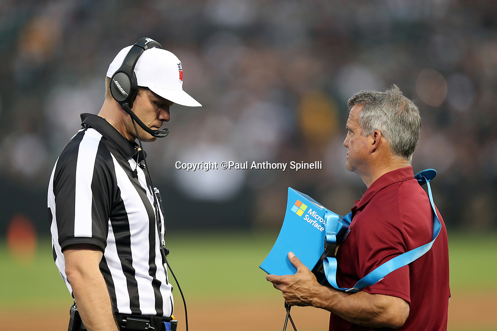 NFL referee Clay Martin (19) looks at a replay a portable tablet on the field during an official review during the Oakland Raiders 2017 NFL week 4 preseason football game against the Seattle Seahawks, Thursday, Aug. 31, 2017 in Oakland, Calif. The Seahawks won the game 17-13. (©Paul Anthony Spinelli)