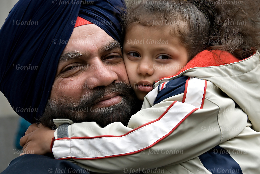 Sikh Father and daughter at the Sikh Day Parade in New York City looking into the camera. <br /> <br /> Example of ethnic pride, man with turban usually means he's a Sikh. Religion is called Sikhism, come from the state of Punjab in India, believe in one g-d and do not worship idols, fifth largest monotheistic religion. call g-d &quot;Wahegura&quot; meaning &quot;the supreme teacher&quot; never cut their hair, believe that men and women are born equal, in monogamy and reincarnation.