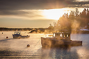 Sea smoke rises among several lobster boats in the small fishing village of Five Islands.  The warm glow of the sun belies the extreme cold necessary to create this dramatic ocean mist.
