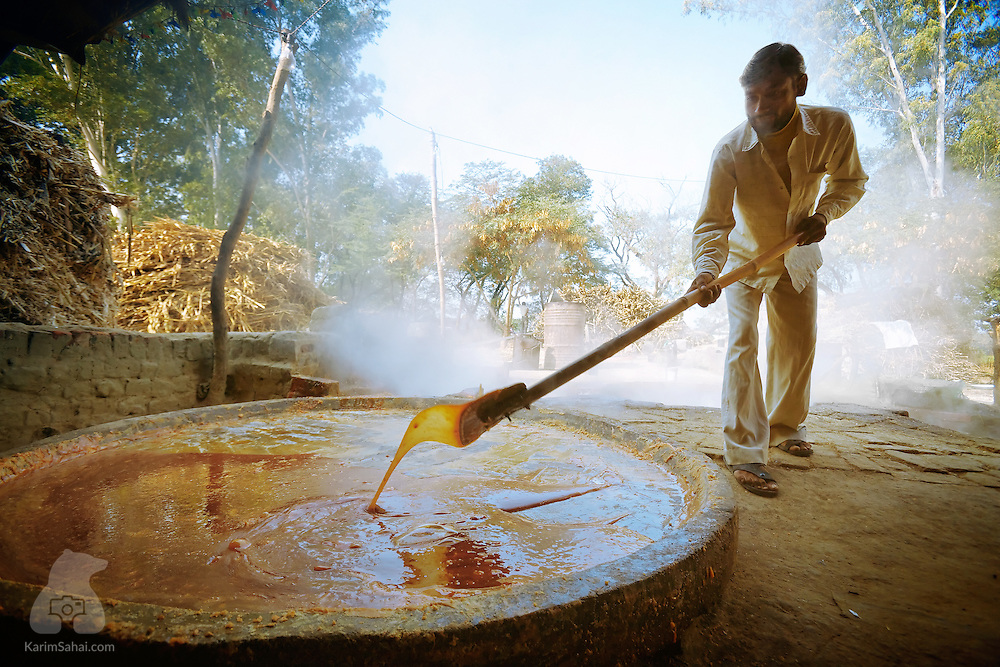 A man prepares jaggery on a large pan, Punjab, India.<br />