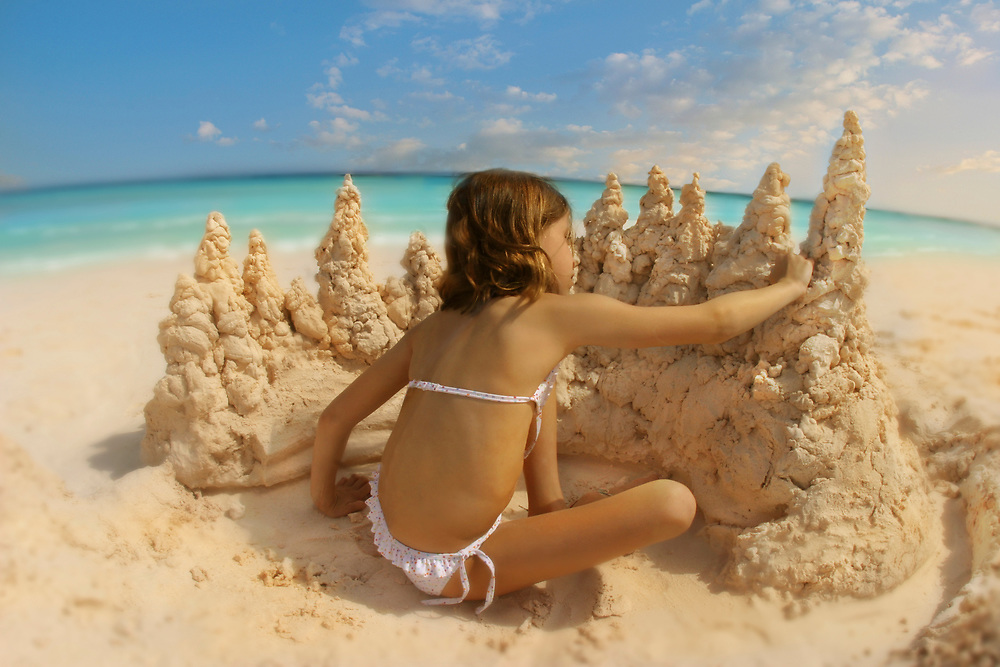 Young girl building a sand castle on a beach