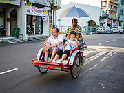 06 OCTOBER 2014 - GEORGE TOWN, PENANG, MALAYSIA: Chinese tourists ride a trishaw (bicycle powered rickshaw) in George Town (also Georgetown), the capital of the state of Penang in Malaysia. Named after Britain's King George III, George Town is located on the north-east corner of Penang Island. The inner city has a population of 720,202 and the metropolitan area known as George Town Conurbation which consists of Penang Island, Seberang Prai, Kulim and Sungai Petani has a combined population of 2,292,394, making it the second largest metropolitan area in Malaysia. The inner city of George Town is a UNESCO World Heritage Site and one of the most popular international tourist destinations in Malaysia.      PHOTO BY JACK KURTZ