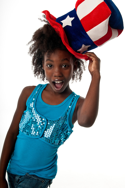 African American girl playing with a very patriotic hat and happy.