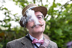 "© Licensed to London News Pictures. 04/05/2019. London, UK. Barry ""Fingers"" Copson, a member of the Handlebar Club, smokes a cigar at the start of the annual Tweed Run bicycle ride, in which participants cycle around the capital wearing vintage tweed outfits. Photo credit: Rob Pinney/LNP"