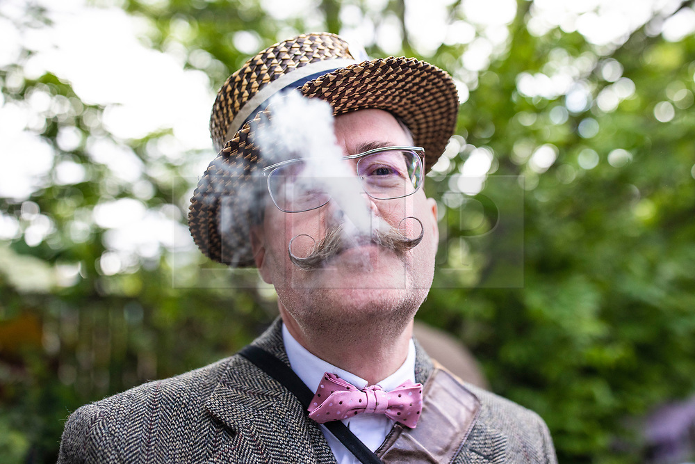 """© Licensed to London News Pictures. 04/05/2019. London, UK. Barry """"Fingers"""" Copson, a member of the Handlebar Club, smokes a cigar at the start of the annual Tweed Run bicycle ride, in which participants cycle around the capital wearing vintage tweed outfits. Photo credit: Rob Pinney/LNP"""
